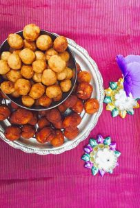Plate of brownish round vella seedai with a bowl of lighter coloured uppu seedai on top, on a petunia pink silk fabric. Small silver lamps and a purple flower on the side