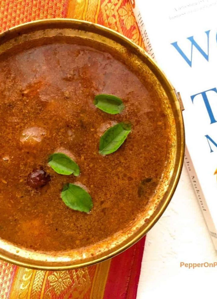 Brown coloured sambar in a brass bowl, with green curry leaves and pale white and red small onions floating on top. The bowl rests on an orange and red zari silk saree and has a white book with blue letters on Tamil merchants, on the right. All on a white background