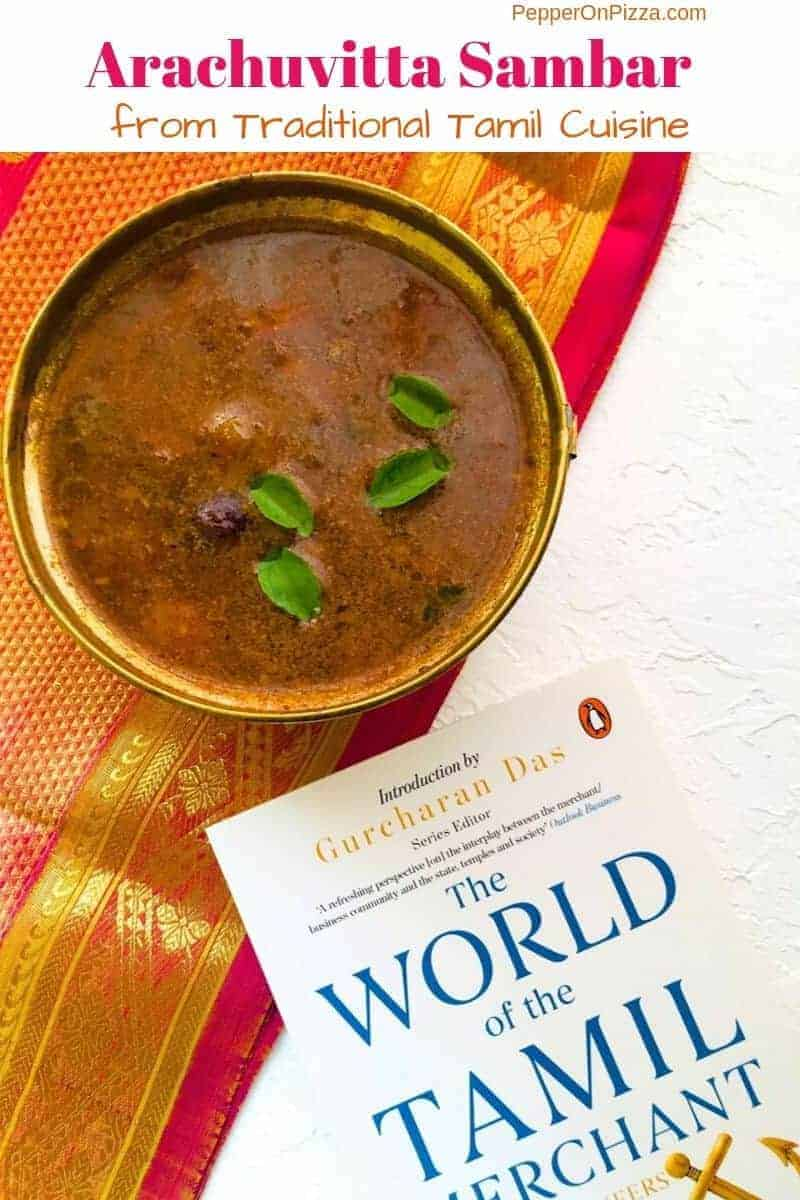 A brass bowl filled with brown coloured gravy arachuvitta sambar, with small onions and curry leaves on the surface. Resting on an orange and red zaree silk saree, with a white book with blue letters on the bottom right. All on a white background. https://www.PepperOnPizza.com