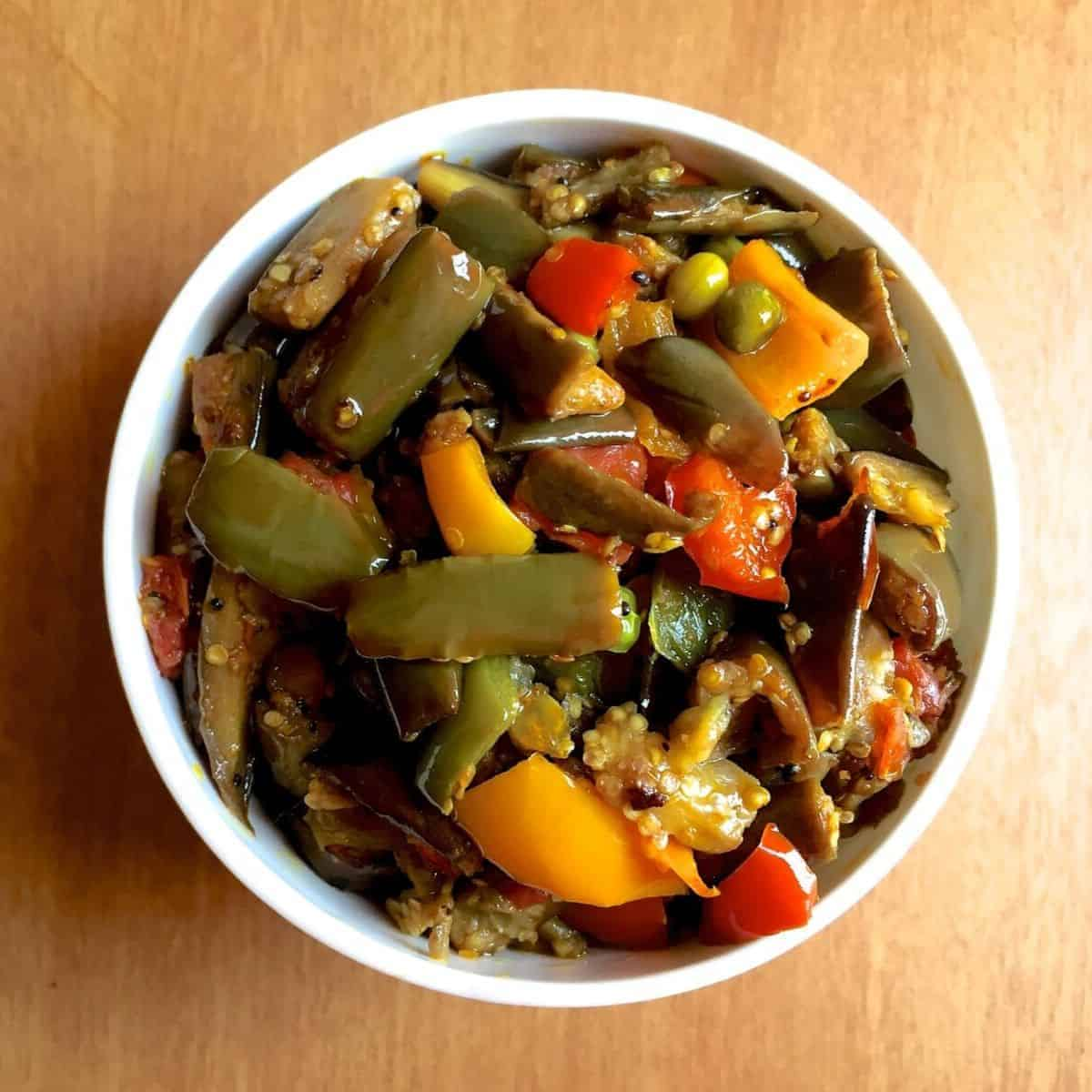 Eggplant/ Brinjal fried with capscium tomato and peas, in a white bowl, on a yellow background