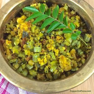 Green and yellow dry curry in a brass bowl with a sprig of curry leaves on top, a pink and white napkin seen to the bottom left. Kothavarangai Paruppu Usili, tender cluster beans sliced thin and cooked with a paste of cooked lentils, tempered with mustard and chili.