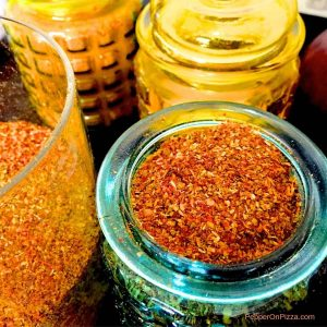 Blue yellow and orange jars with rusty orange coloured rasam powder, a homemade spice powder from Indian Tamil cuisine