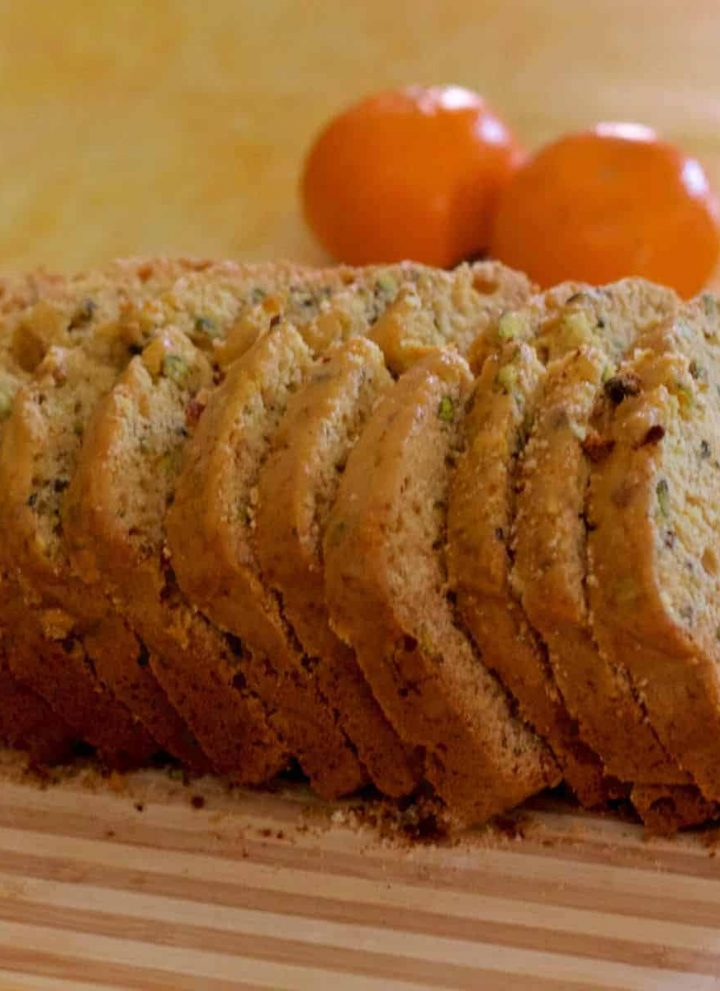 Slices of pale golden orange honey pistachio cake, on a striped board, with 2 bright oranges in the background, all on a pale yellow backdrop