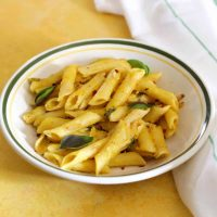 Penne pasta in a yellow pumpkin sauce with green basil leaves and red chili flakes, on a white pasta plate edged with green, on a yellow background. A white napkin with thin green stripes on the right