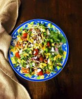 Bright green red and yellow Pearl barley tomato avocado salad with microgreens, on a plate edged with large blue and yellow scrolled design.