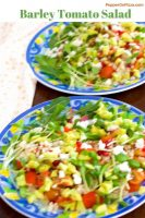 Green red yellow white Pearl Barley salad with tomato, avocado, microgreens, on two plates edged with blue and yellow flowered design. White napkin with orange polka dots on the left. https://www.PepperOnPizza.com