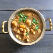 Thiruvathirai Ezhukari kootu, a stew from 7 vegetables in a brown tamraind gravy, garnished with cilantro, in a 2 handled brass bowl, on a gray wooden background
