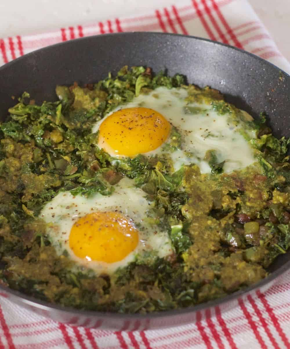 Two open faced eggs on a sauce of sauteed kale and onion with a parsley pesto