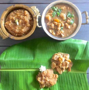 Thiruvathirai Kali, a brown coloured sweet dish, in a brass bowl and some spread on a green banana leaf. Vegetable stew in another bowl and on the leaft, with a pat of white butter by the side