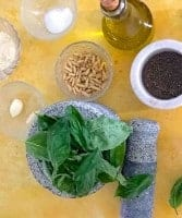 Ingredients for making pesto: A stone mortar with basil leaves, the pestle by its side; a glass bowl with roasted pine nuts, another with 2 cloves of garlic, a small mortar with groud black pepper, a bottle of olive oil, a bowl of grated parmesan and another of salt