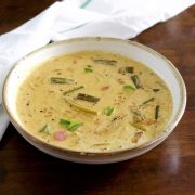 Pale yellow creamy raw mango curry with okra, shallots, mango and curry leaves floating on top, in a white bowl edged with beige. On a dark brown background with a white napkin with green stripe behind