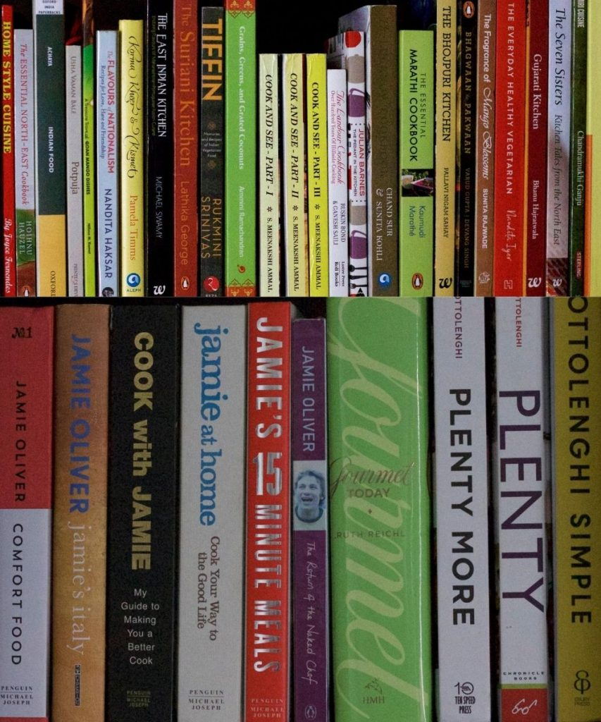 Rows of different coloured cookbooks on two shelves for cooking from cookbooks