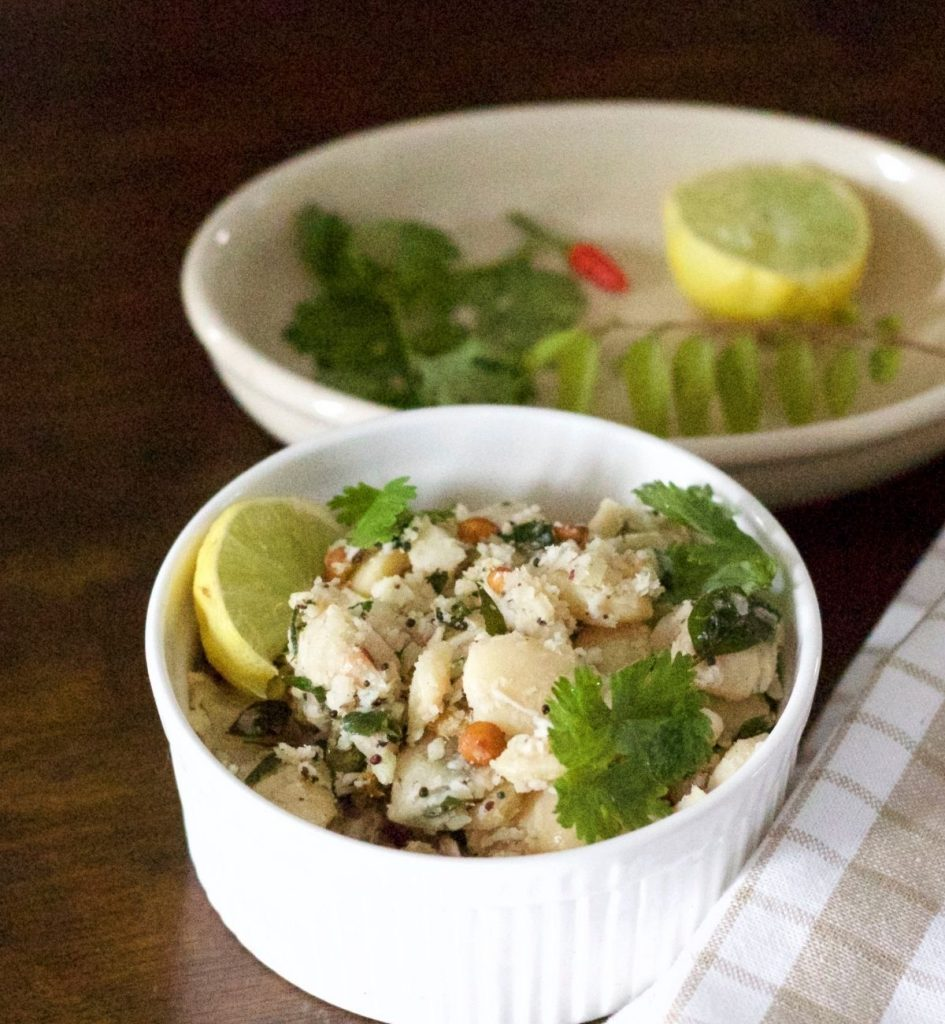 White bowl filled with white double beans mochai Sundal with tempering of channa dal, mustard, garnished with coconut and coriander leaves and a slice of lemon at one side. A beige and white napkin to the right and a plate with lemon, red chili and curry leaves, coriander leaves at the back