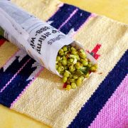 Cooked dry green peas with coconut raw mango and peanuts wrapped in a roll of newspaper resting on a sand and pink coloured mat on a yellow background