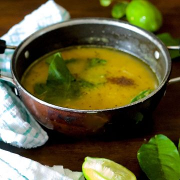 Pale yellow cooked lentils with gondhoraj lime leaves, green chili and radhuni spices seen on top. Green lime and leaves at background and foreground with slice of lime. Green and white napkin to the right. All on a brown wooden background