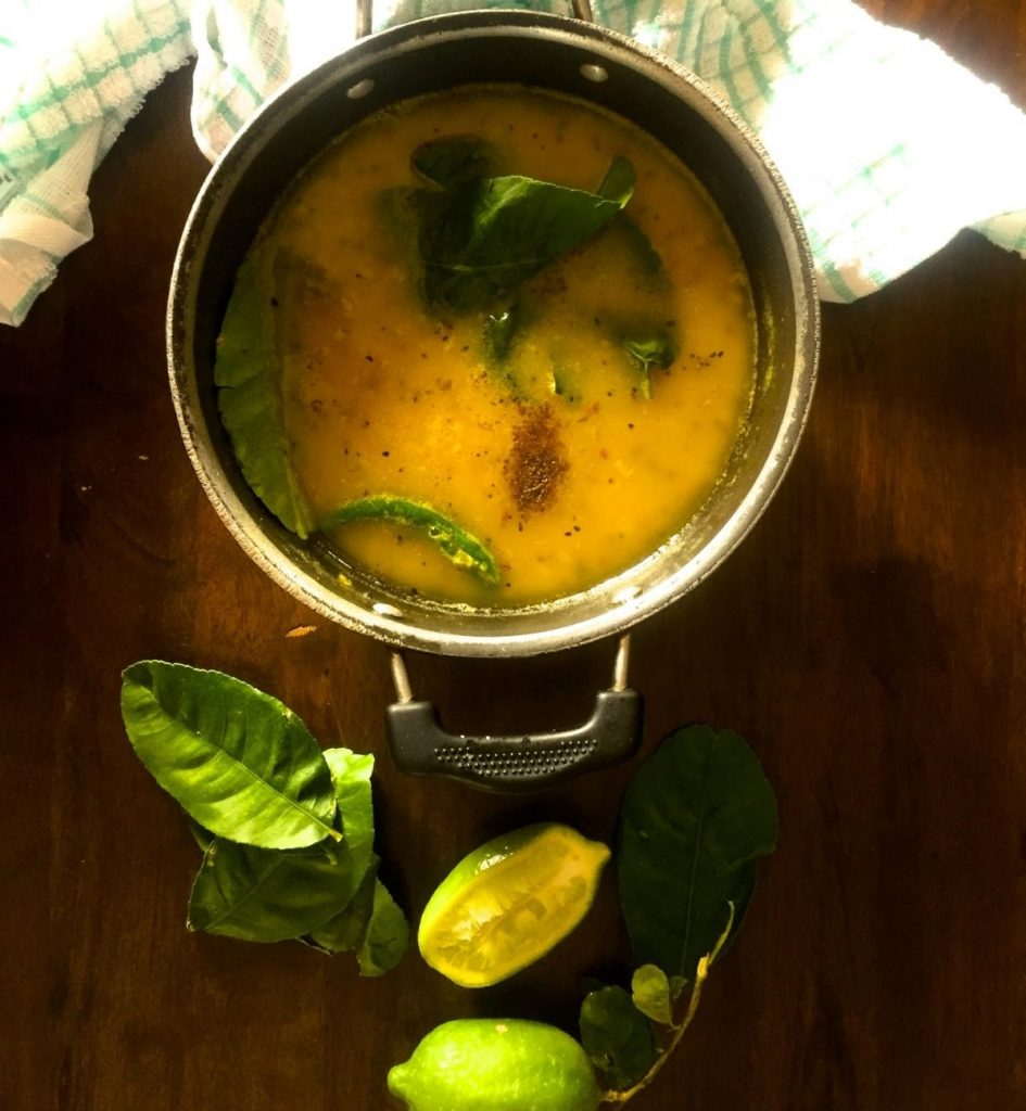 Pale yellow cooked lentils in a frying pan. Green chili, Lime leaves and brown spices on the surface. Lime leaves, sliced lime, whole green lime with stalk and leaves, all vertically below the pan.On a brown wooden background. Green and white napkin above in back ground