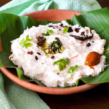 Clay bowl with a green banana leaf filled with white curd and rice, with garnish of green cilantro leaves and tempering of chilies and mustard seeds in oil, with a mango pickle seen on one side. A pale green napkin to the left