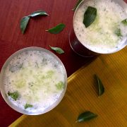 Tall steel glasses of Neer Mor, buttermilk. Green grated cucumber and curry leaves are seen floating on top. A green gold striped saree on the right, curry leaves everywhere, all on a reddish brown background
