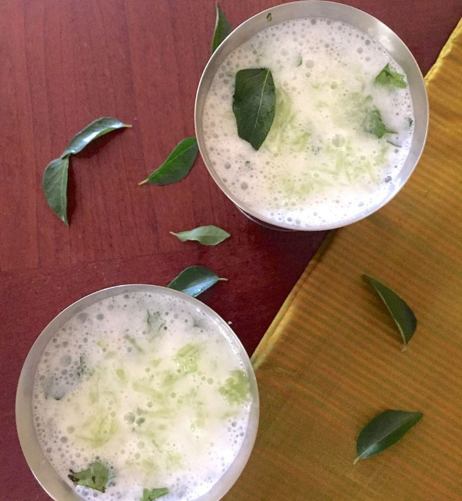 Two steel tumblers with white buttermilk, neer mor with grated cucumber, garnished with green curry leaves. A gold/ green striped silk fabric to the right and curry leaves strewn all over. All on a redding brown background