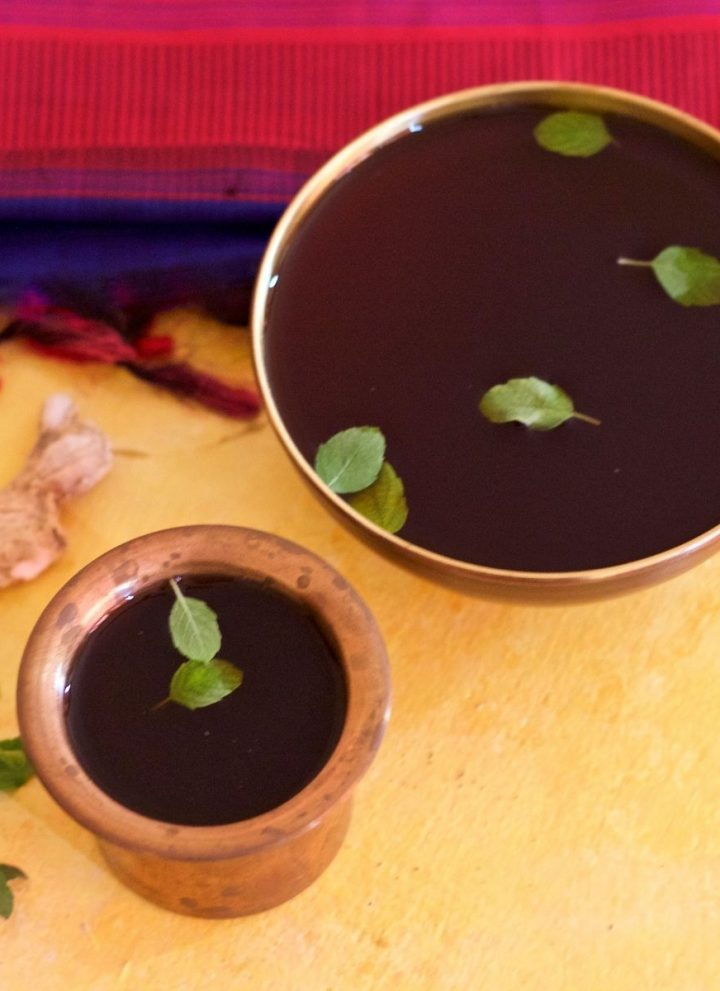 Panakam, brown jaggery and dry ginger drink in a brass tumbler and a brass bowl, garnished with green tulsi leaves, dry ginger piece and tulsi leaves on the left, red and blue silk saree in the background. All on a yellow background