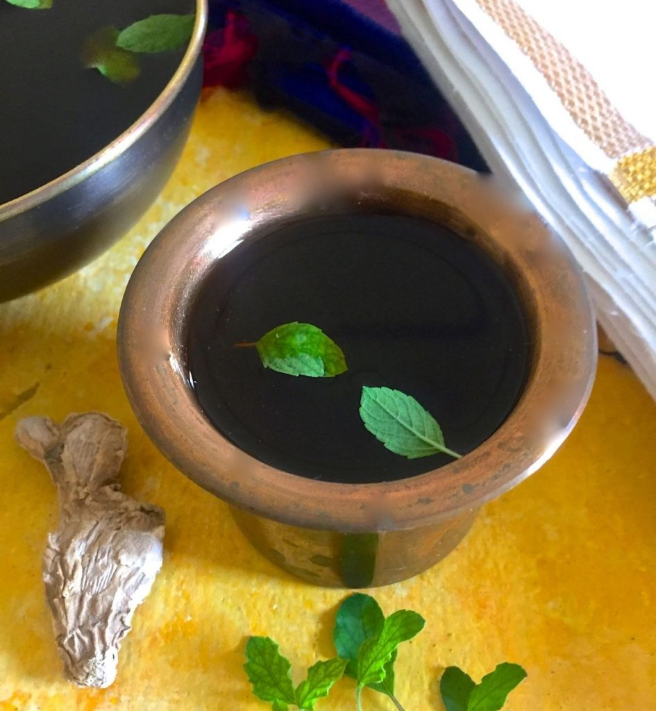 Brass tumbler filled with dark brown Panakam drink, garnished with bright green tulsi leaves. Piece of dry ginger and stalk of tulsi leaves in the foreground. Another dark bowl of the liquid partly seen on the left. A white dhothi with zari border seen on the right. All on a yellow background