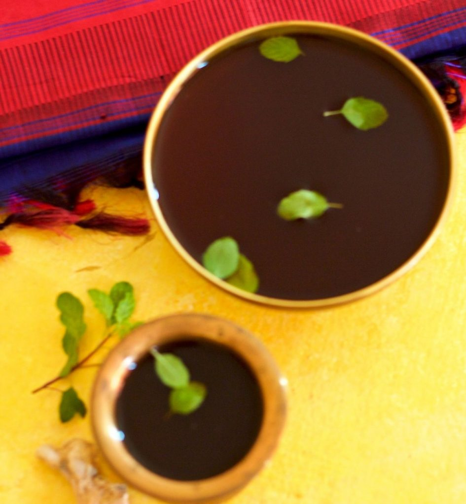 Dark brown jaggery liquid in brass tumbler and a brass bowl, garnished with green sacred basil leaves.On a yellow background and a blue and red silk fabric in the background