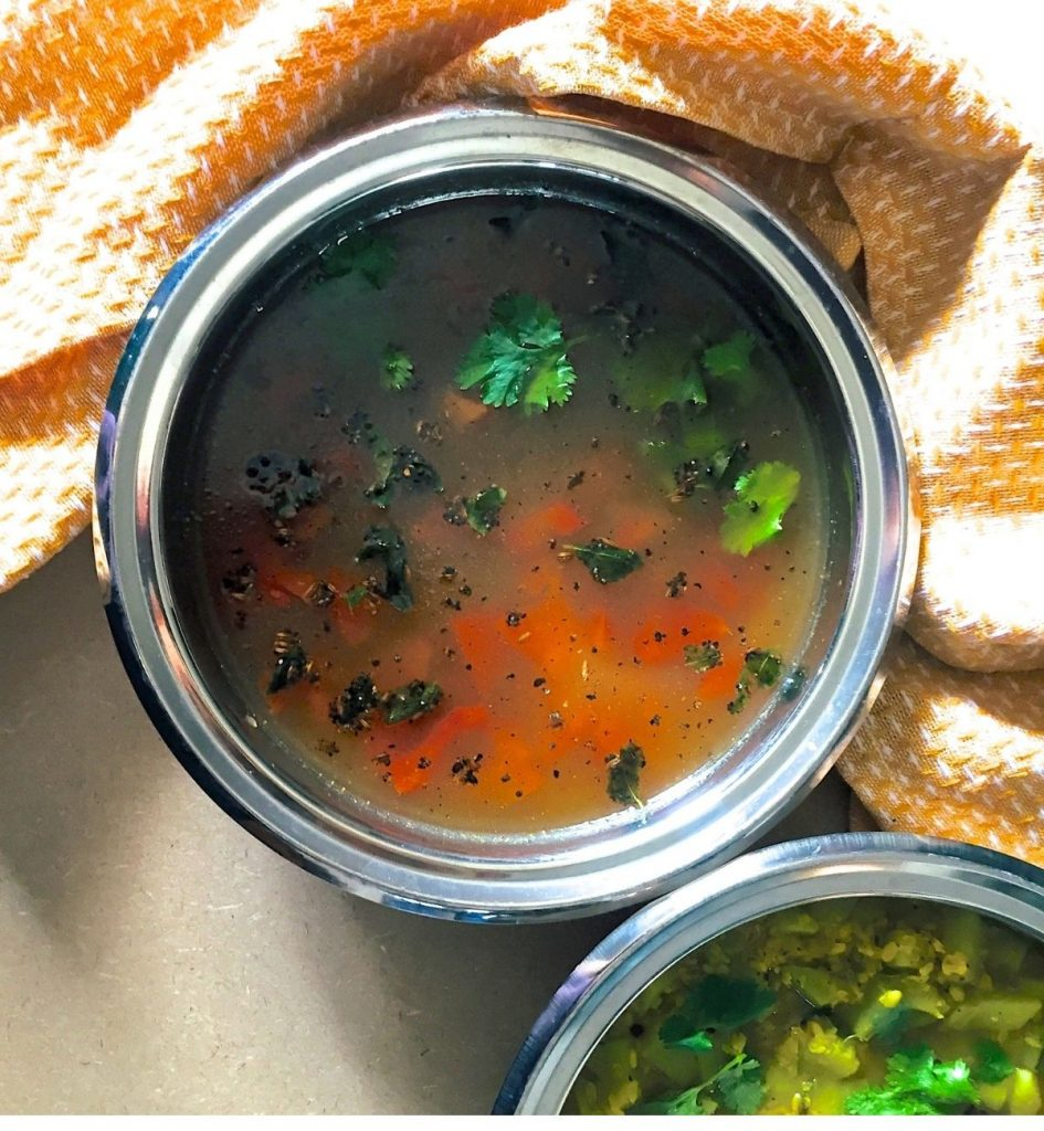 Overhead view of orange yellow liquid gravy with garnish of green coriander leaves and tempering of curry leaves adn cumin seeds, with slices of red tomato visible. Another bowl partly seen with green yellow vegetable curry. Orange napkin to the right