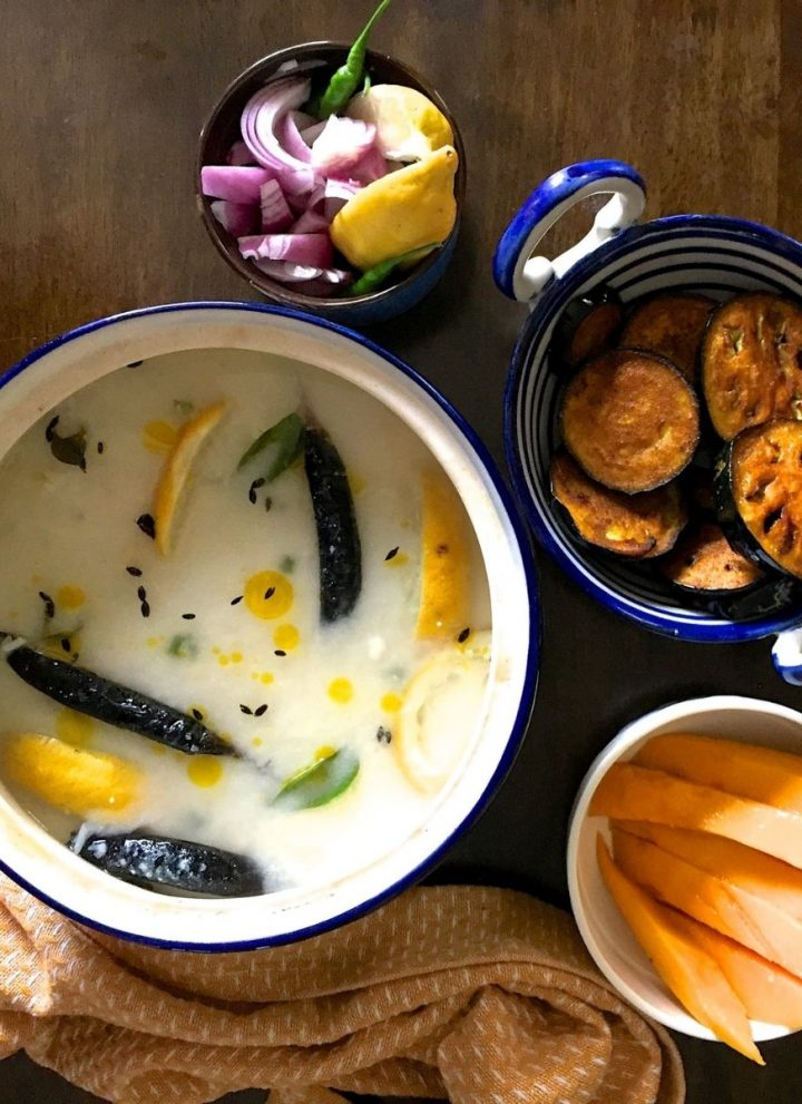 White mixture of Chunka Dahi Pakhala Bhaat, cooked rice soaked in water and curd, in a blue rimmed pot. Slices of lemon, curry leaves, fried cumin and chilies seen on the surface. Bowl of sliced yellow mangoes and fried brinjal slices in a blue pottery pan with handles on the right, a mustard yellow napkin with white fletches on the left and bottom of the pot.
