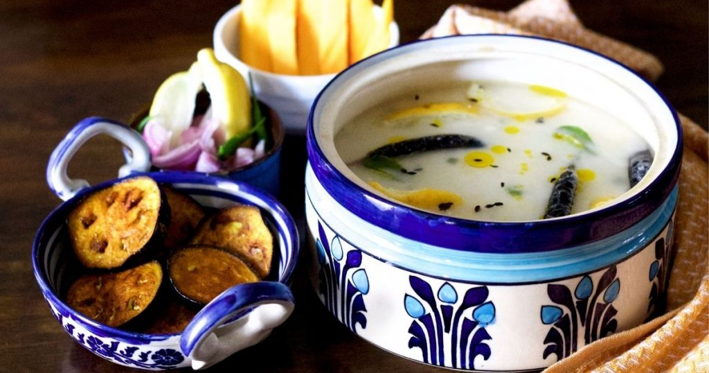 Cooked rice covered by water and curd in a blue and white designed pottery container, with slices of yellow lime, green curry leaves, black fried chilies and cumin floating on the surface. A blue and white pottery pan with handles on the left, filled with fried brinjal slices. A bowl of sliced onion, green chili and lemon slices and a white bowl with yellow mango slices to the left. A mustard cloth with white thread work on the right.