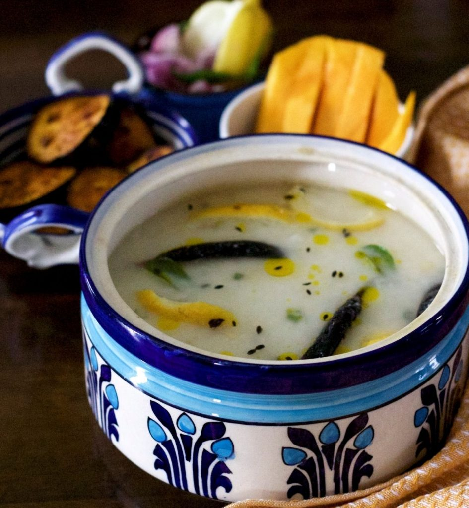 Large blue and white clay pot with white chunka dahi pakhala, being cooked rice in water and curd, with yellow lime slices, black friend chili and cumin seeds, green curry leaves and drops of yellow mustard oil seen on the surface. In the backdrop, bowls with yellow mango slices, fried eggplant slices, onion, green chili and lime slices. A mustard and white napkin to the right.