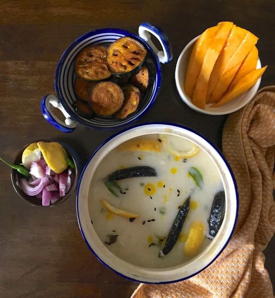 Blue and white rimmed pot with white mixture of cooked rice, water and curd. Chlies, curry leaf, lemon slices, cumin seeds seen on the surface. A bowl with sliced pink onion, yellow lime slices, green chili seen to the left. Bowls with mango slices, fried eggplant slices at the back and a mustard yellow and white napkin to the right