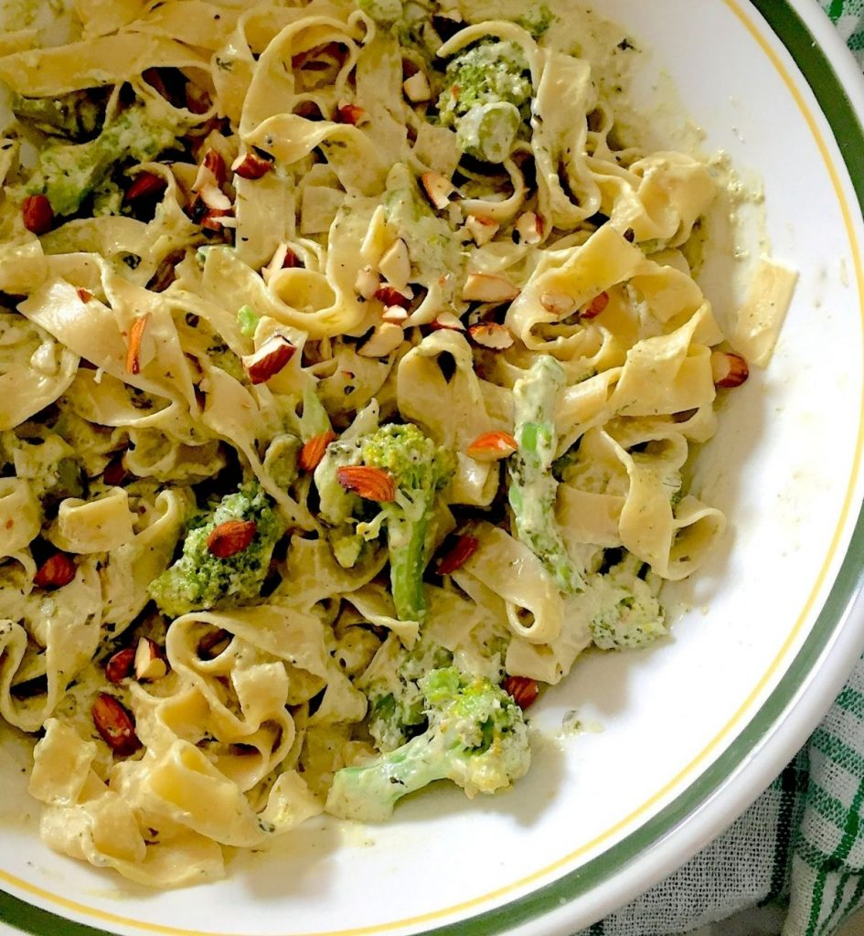 Fettuccine pasta in a creamy white sauce with Broccoli, asparagus and almond slices in a white bowl with green and yellow edging. A green and white napkin at the sides. Broccoli Asparagus Pesto Pasta