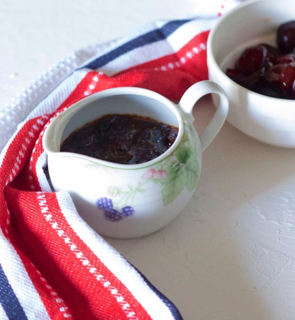 Dark red thick Cherry Compote in a white china jar with design of purple fruits, pink flowers and green leaves. Red white black striped napkin to the left. White bowl with sliced cherries in the background. All on a white background
