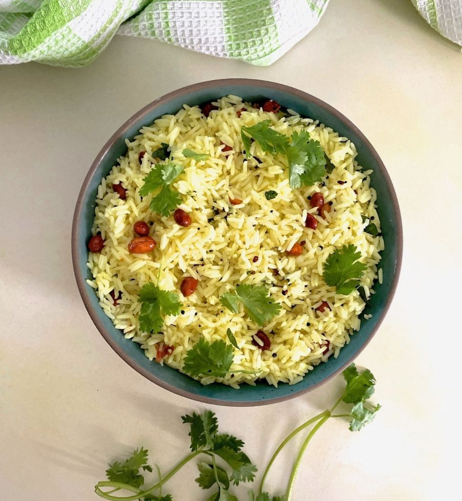 Blue-green bowl edged with brown with pale yellow lemon rice garnished with fried peanuts and fresh green coriander leaves. A green and white napkin seen at the top of the image and green coriander leaves at the bottom