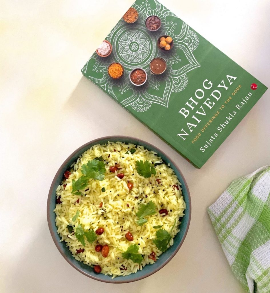 Bowl of yellow coloured rice. Garnish of brown fried peanuts seen on top with green cilantro/coriander leaves. Dark green book on food seen on the top right and green and white checked napkin bottom right. On a pale grey background tinged with yellow