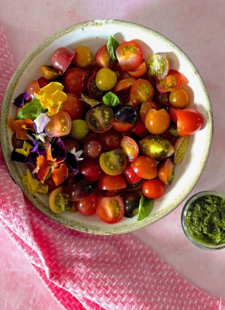 White bowl edged with pale green, filled with heirloom tomato basil salad of sliced colourful cherry tomatoes, red, orange, green, black garnished with edible flowers and basil leaves. On a pale pink surface with a pink napkin to the left. Glass bowl with green basil dressing to the right