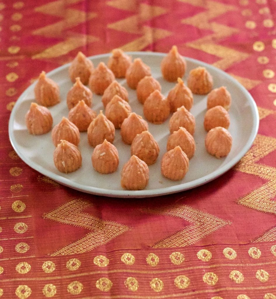 Pale pink orange conical modaks with pointed tops, on a white ceramic plate. On a pink and gold silk fabric background